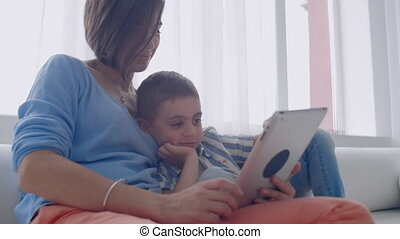 Mother and son playing with digital tablet at home. Young...