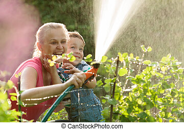 Mother and son playing with water