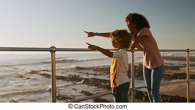 Mother and son pointing away the sea - Side view of mixed ...