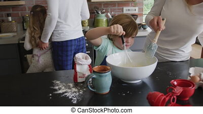 Mother and son preparing cookie on worktop in kitchen at ...