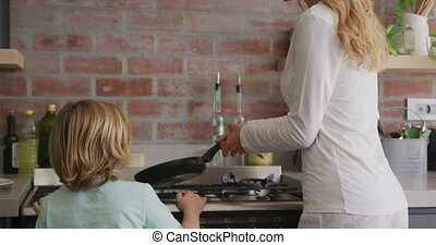 Mother and son preparing food in kitchen at comfortable home 4k