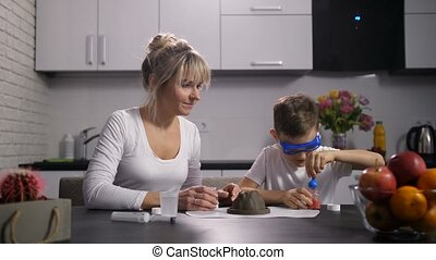 Mother and son preparing reagents for experiment - Adult mom...