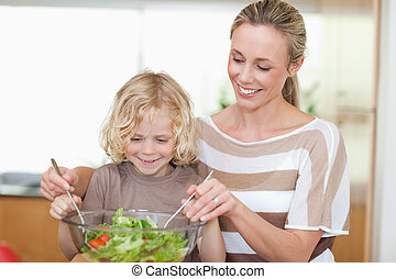 Mother and son preparing salad