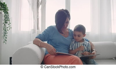 Mother and son read books. Happy young mother and son read...