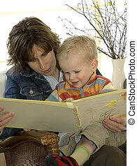 Mother and son reading a book on a chair
