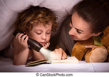 Mother and son reading book under blanket