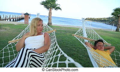 Mother and son relaxing in a hammock near the sea