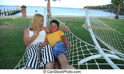 Mother and son relaxing in a hammock