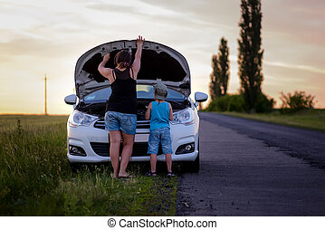 Mother and Son Repairing Something on their Car