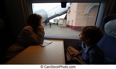 Mother and son riding on train and look out window
