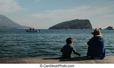 Mother and son sit on an old pier on the seashore harbor some distance apart.