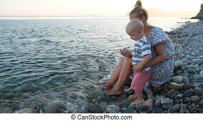 Mother and son sit on the beach at sunset