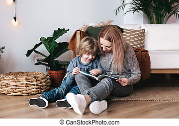 Mother and son sitting and reading book together at home