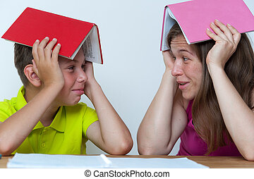 Mother and son sitting at the table with books