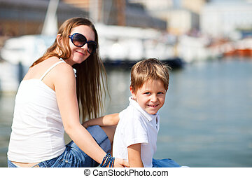 Mother and son sitting on jetty in city center