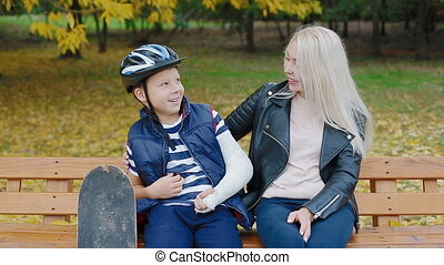 Mother and son sitting on the bench in the park - Caucasian...