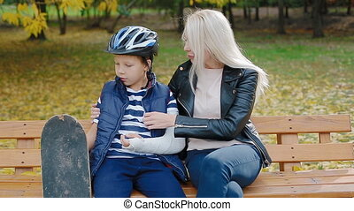 Mother and son sitting on the bench in the park