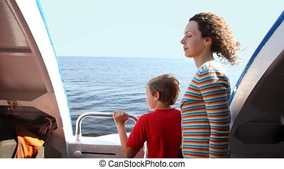 Mother and son stand at side of fast moving boat hydrofoil on sea