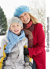 Mother And Son Standing Outside In Snowy Landscape