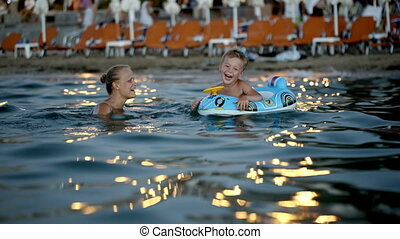 Mother and son swimming in the evening