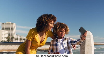 Mother and son taking selfie at beach - Front view of mixed ...