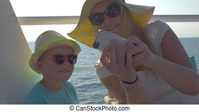 Mother and son taking selfie during sea travel