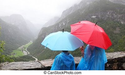 mother and son in raincoats and under umbrellas look valley in woody mountains