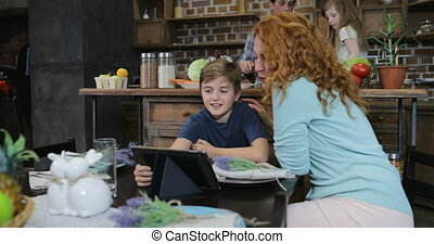 Mother And Son Use Digital Tablet While Father With Daughter Salting Vegetables For Dinner Salad In Kitchen