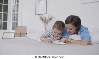 Mother and son using digital tablet in bedroom at home....