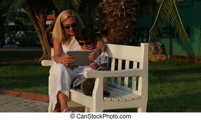 Mother and son using digital tablet