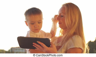 Mother and son using tablet on vacation at sunset.