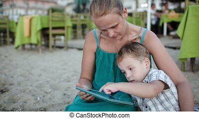 Mother and son using tablet PC near beach cafe