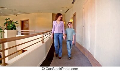 Mother and son walk along corridor, girl goes at background