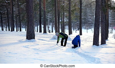 Mother and son walk in the winter forest. They throw snow...