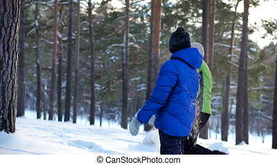 Mother and son walk in the winter forest. They throw snow at...