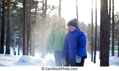 Mother and son walk in the winter forest. They throw up the...