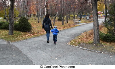 Mother and son walking in autumn park