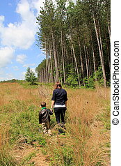 Mother and son walking in meadow
