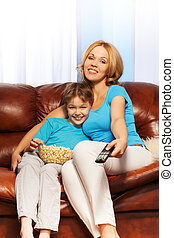 Mother and son watching television with popcorn