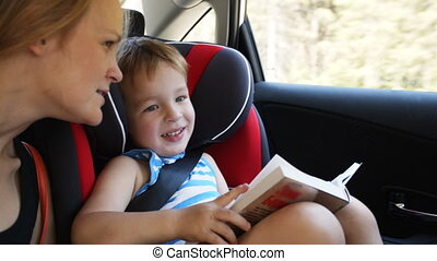 Mother and son with book traveling by car