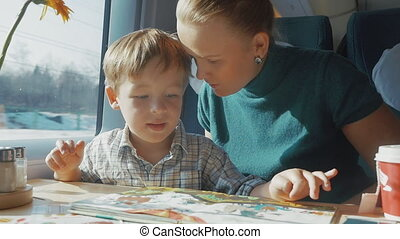 Mother and son with childrens book in the train