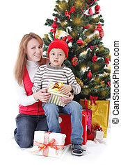 Mother and son with gifts under Christmas tree