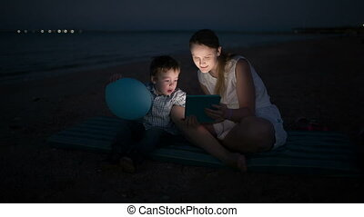 Mother and son with pad by the sea at night