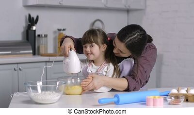 Mother and special needs girl mix dough with mixer