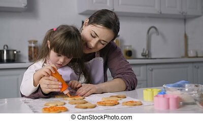 Portrait of loving mother and cute little daughter with down syndrome decorating homemade cookies with icing. Positive special needs child helping mom to decor freshly baked biscuits in kitchen.