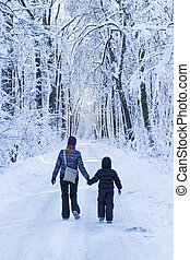 Mother and sun walking together on a forest track in winter time