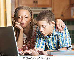 Mother and teen son work in kitchen on laptop - Mother...