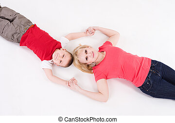 Mother and the son lie on a floor having joined hands.