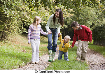 Mother and three young children walking on path outdoors smiling