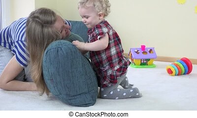 mother and toddler child play with blue big pillow and show...